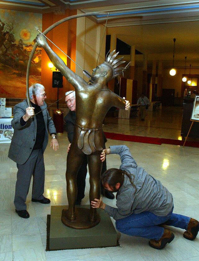 FILE - in this Feb. 6, 2002 file photo, Salina sculptor Richard Bergen, left, former state Sen. Ben Vidricksen, center, and Bergen's son, Rich Bergen, slide an 8-foot-tall version of the