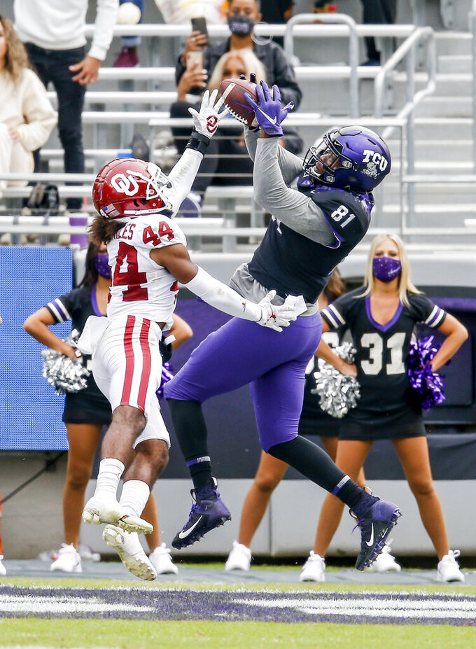 TCU tight end Pro Wells (81) catches a pass for a touchdown as Oklahoma defensive back Brendan Radley-Hiles (44) defends during the second half of an NCAA College football game, Saturday, Oct. 24, 2020, in Fort Worth, Texas. Oklahoma won 33-14. (AP Photo/Brandon Wade)