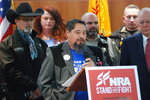 Mayor Nathan Dial of Estancia, N.M., center, speaks at a news conference about gun legislation on Friday, Jan. 31, 2020, in Santa Fe, N.M., as hundreds of advocates for 2nd Amendment rights rallied outside the Statehouse against a proposed red-flag gun law. A bill supported by Democratic Gov. Michelle Lujan Grisham would allow law enforcement officials or family members to seek court orders to seize firearms temporarily from people deemed a threat to themselves or others. (AP Photo/Morgan Lee)