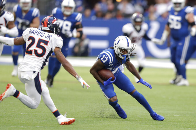 Indianapolis Colts' T.Y. Hilton (13) is tackled by Denver Broncos' Chris Harris (25) during the second half of an NFL football game, Sunday, Oct. 27, 2019, in Indianapolis. (AP Photo/Michael Conroy)