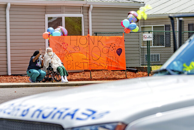 In this Wednesday, May 6, 2020 photo, Ruth Evelyn Harrington, right, and certified nursing assistant Stacie Coleman wave during a birthday party for Harrington at River's Bend Retirement Community, in Kuttawa, Ky. The parade marked Harrington's 109th birthday, which could not be held in person due to restrictions in the midst of the COVID-19 pandemic. (Dave Thompson/The Paducah Sun via AP)
