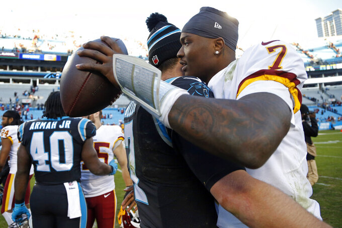 Carolina Panthers quarterback Kyle Allen and Washington Redskins quarterback Dwayne Haskins (7) hug following an NFL football game in Charlotte, N.C., Sunday, Dec. 1, 2019. (AP Photo/Brian Blanco)