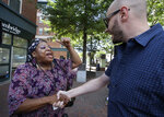 Maribel Ortiz, of Cambridge, Mass., shakes hands with Ryan Hanslik, of Waltham, Mass., Monday, July 15, 2019, in Cambridge, as they debate about President Trump's tweets ordering American congresswomen of color, including U.S. Rep. Ayanna Pressley, D-Mass., to go back to where they came from. (AP Photo/Elise Amendola)