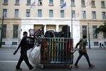 Migrants from Bangladesh push a trolley with collected plastic items as they pass in front the Bank of Greece headquarters in Athens, Thursday, Jan. 16, 2020. (AP Photo/Thanassis Stavrakis)