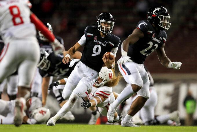 Cincinnati quarterback Desmond Ridder, center, carries the ball during the second half of an NCAA college football game against Houston, Saturday, Nov. 7, 2020, in Cincinnati. (AP Photo/Aaron Doster)