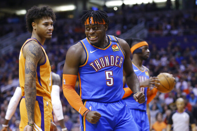Oklahoma City Thunder guard Luguentz Dort (5) shouts after being fouled by Phoenix Suns forward Kelly Oubre Jr., left, as Thunder center Nerlens Noel, right, holds the ball during the first half of an NBA basketball game Friday, Jan. 31, 2020, in Phoenix. (AP Photo/Ross D. Franklin)