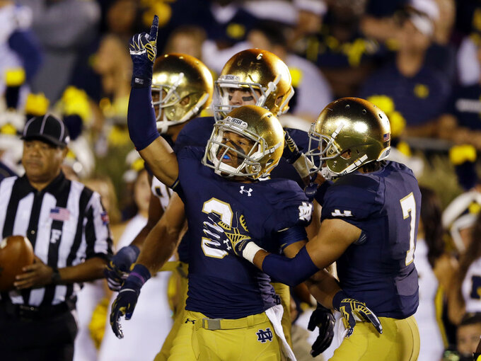 FILE - In this Sept. 6, 2014, file photo, Notre Dame wide receiver Amir Carlisle, center, celebrates a touchdown against Michigan during the first half of an NCAA college football game in South Bend, Ind. Notre Dame defeated Michigan 31-0. (AP Photo/Michael Conroy, File)