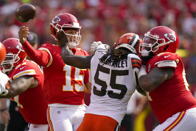Kansas City Chiefs quarterback Patrick Mahomes (15) throws over Cleveland Browns defensive end Takkarist McKinley (55) during the first half of an NFL football game against the Cleveland Browns Sunday, Sept. 12, 2021, in Kansas City, Mo. (AP Photo/Charlie Riedel)
