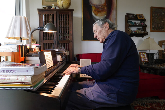 """Peter Fuchs plays the piano at his home in Aventura Fla., Tuesday, Feb. 23, 2021. Fuchs and his wife Veronica host a Facebook Live show called """"Stump the Maestro"""". At the start of the show Fuchs plays tunes that viewers try to guess. Then viewers request songs, mostly Broadway show tunes, '50s classics, movie soundtracks, jazz standards and some Beatles music, and Fuchs is a former Broadway composer, conductor and Holocaust survivor. (AP Photo/Marta Lavandier)"""