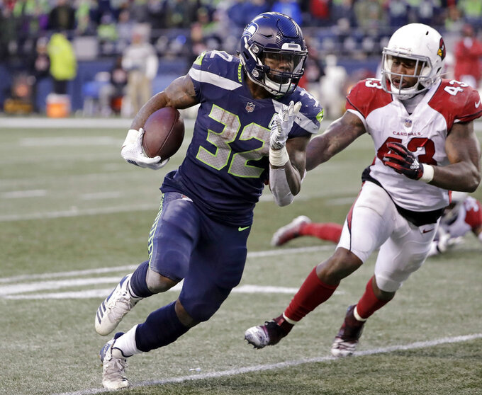 FILE - In this Sunday, Dec. 30, 2018 file photo, Seattle Seahawks' Chris Carson carries as Arizona Cardinals' Haason Reddick (43) pursues during the second half of an NFL football game in Seattle. Seattle takes the league's No. 1 rushing offense into a wild-card meeting with the Cowboys on Saturday night, Jan. 5, 2019 led by Chris Carson but with more help from others than your average pro backfield.(AP Photo/Ted S. Warren, File)