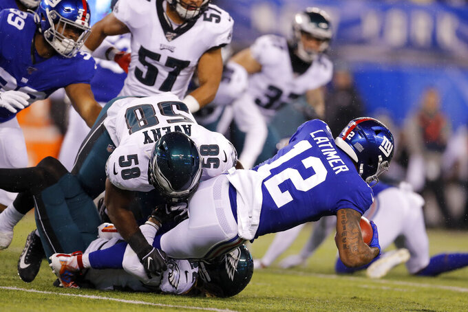 New York Giants wide receiver Cody Latimer (12) is stopped by Philadelphia Eagles defensive end Genard Avery (58) in the first half of an NFL football game, Sunday, Dec. 29, 2019, in East Rutherford, N.J. (AP Photo/Adam Hunger)