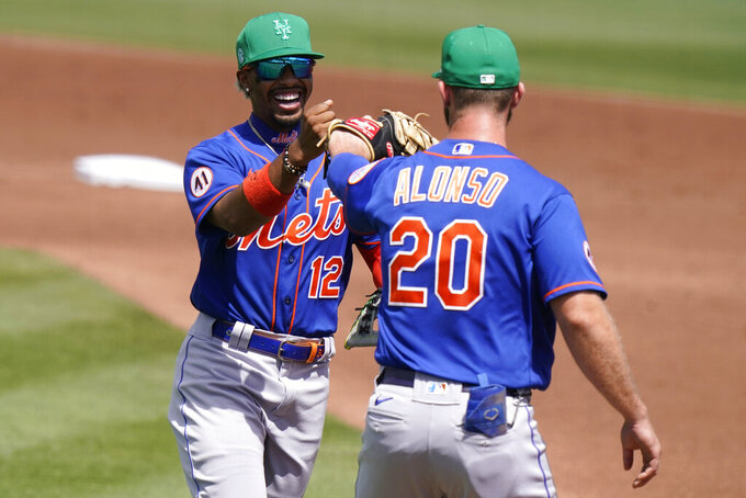 New York Mets shortstop Francisco Lindor (12) bumps fists with first baseman Pete Alonso (20) after Miami Marlins' Jorge Alfaro ground out to Lindor to end the second inning during a spring training baseball game, Wednesday, March 17, 2021, in Jupiter, Fla. (AP Photo/Lynne Sladky)