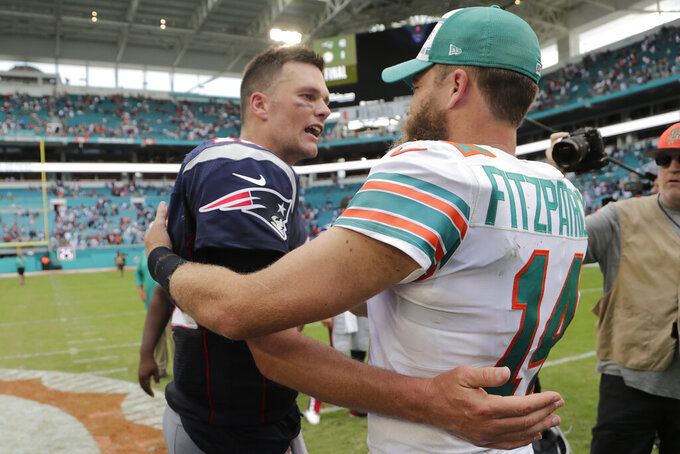 New England Patriots quarterback Tom Brady (12) and Miami Dolphins quarterback Ryan Fitzpatrick (14), greet each other at the end of an NFL football game, Sunday, Sept. 15, 2019, in Miami Gardens, Fla. The Patriots defeated the Dolphins 43-0. (AP Photo/Lynne Sladky)