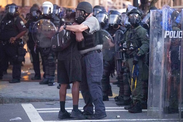 A police officer embraces a protester who helped disperse a crowd of people during a demonstration Monday, June 1, 2020, in Atlanta over the death of George Floyd, who died after being restrained by Minneapolis police officers on May 25. (AP Photo/John Bazemore)
