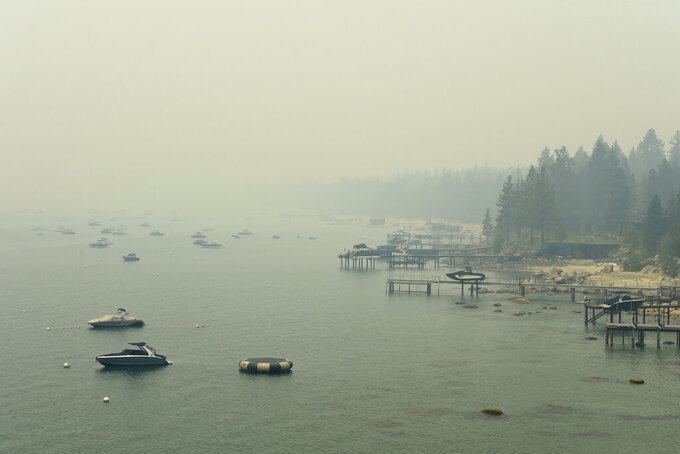 Smoke from Caldor Fire in California covers Lake Tahoe in the Incline, Nev., area on Tuesday, Aug. 24, 2021. A California fire that gutted hundreds of homes advanced toward Lake Tahoe on Wednesday as thousands of firefighters tried to box in the flames and tourists who hoped to boat or swim found themselves looking at thick yellow haze instead of alpine scenery. (Andy Barron/The Reno Gazette-Journal via AP)