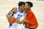 Miami guard Isaiah Wong, right, reaches in to guard Pittsburgh guard Nike Sibande (22) during the second half an NCAA college basketball game in the first round of the Atlantic Coast Conference tournament in Greensboro, N.C., Tuesday, March 9, 2021. (AP Photo/Gerry Broome)