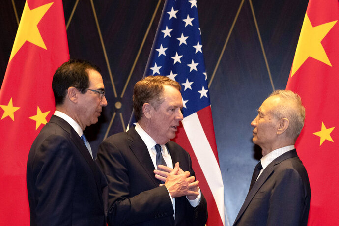 FILE - In this July 31, 2019, file photo U.S. Trade Representative Robert Lighthizer, center, gestures as he chats with Chinese Vice Premier Liu He, at right with Treasury Secretary Steven Mnuchin, left, looking on after posing for a family photo at the Xijiao Conference Center in Shanghai. The 13th round of U.S.-China trade negotiations is set to begin Thursday, Oct. 10 in Washington. (AP Photo/Ng Han Guan, Pool, File)