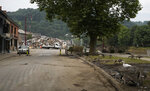 Geese and other birds feed on the side of a road in front of a pile of damaged household goods discarded in the town square after flooding in Vaux-sous-Chevremont, Belgium, Saturday, July 24, 2021. Residents were still cleaning up after heavy rainfall hit the country causing flooding in several regions. (AP Photo/Virginia Mayo)