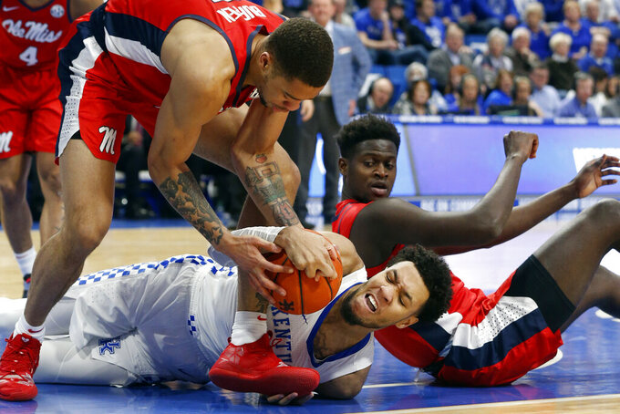 Kentucky's EJ Montgomery battles for the ball between Mississippi's KJ Buffen, top, and Khadim Sy, right, in the first half of an NCAA college basketball game in Lexington, Ky., Saturday, Feb. 15, 2020. (AP Photo/James Crisp)