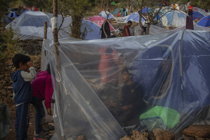 In this Wednesday, Sept. 25, 2019 photo Syrians stand inside their makeshift tent near the refugee and migrant camp at the Greek island of Samos. Greece's conservative government announced Wednesday Nov. 20, 2019, plans to overhaul the country's migration management system, and replacing existing camps on the islands with detention facilities and moving and 20,000 asylum seekers to the mainland over the next few weeks. (AP Photo/Petros Giannakouris)