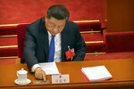 FILE - In this May 28, 2020, file photo, President Xi Jinping reaches to vote on a piece of national security legislation concerning Hong Kong during the closing session of China's National People's Congress (NPC) in Beijing. China's National People's Congress on May 28, 2020 endorsed a national security law for Hong Kong that will require its government to enforce measures to be decided later by leaders in Beijing. The move coincided with recent arrests of Hong Kong pro-democracy advocates who say the law will undermine civil liberties and might be used to suppress political activity. (AP Photo/Mark Schiefelbein, File)