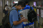 A student plays an online game on his smartphone as he waits for his train at a subway station in Beijing Tuesday, Sept. 14, 2021. China has set new rules limiting the amount of time kids can spend playing online games. (AP Photo/Andy Wong)