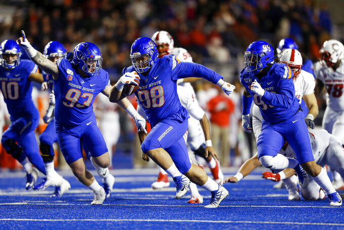 CORRECTS BOISE STATE PLAYER WITH BALL TO SONATANE LUI, INSTEAD OF SCALE IGIEHON - Boise State nose tackle Sonatane Lui, center, runs with the ball for a touchdown after a New Mexico fumble, surrounded by Boise State linebacker Curtis Weaver, right, and defensive tackle Chase Hatada, left, during the first half of an NCAA college football game Saturday, Nov. 16, 2019, in Boise, Idaho. (AP Photo/Steve Conner)