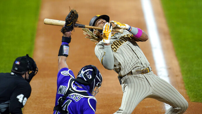 San Diego Padres' Fernando Tatis Jr., right, reacts to a high, inside pitch thrown by Colorado Rockies starting pitcher Jeff Hoffman as catcher Tony Wolters pulls in the throw in the seventh inning of a baseball game, Monday, Aug. 31, 2020, in Denver. The padres won 6-0. (AP Photo/David Zalubowski)