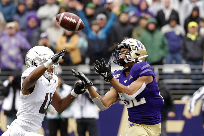 Washington's Jordan Chin, right, reaches to catch a 48-yard touchdown pass as Oregon's Thomas Graham Jr. defends in the first half of an NCAA college football game Saturday, Oct. 19, 2019, in Seattle. (AP Photo/Elaine Thompson)