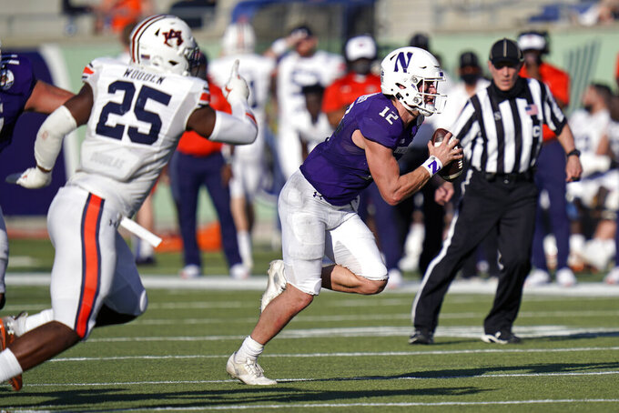 Northwestern quarterback Peyton Ramsey (12) runs past Auburn linebacker Colby Wooden (25) enroute to a 30-yard touchdown run during the second half of the Citrus Bowl NCAA college football game, Friday, Jan. 1, 2021, in Orlando, Fla. Ramsey also threw three touchdown passes in a 35-19 win over Auburn. (AP Photo/John Raoux)