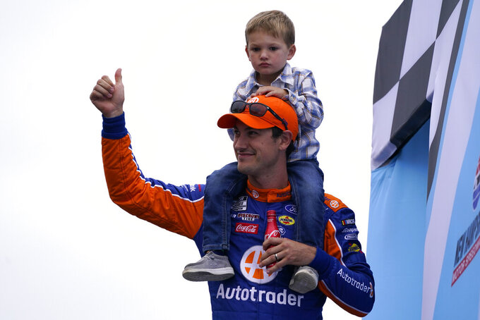 Joey Logano with his son Hudson at a NASCAR Cup Series auto race, Sunday, July 18, 2021, in Loudon, N.H. (AP Photo/Charles Krupa)