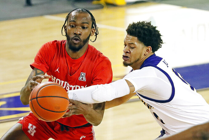 Houston's DeJon Jarreau (3) battles with East Carolina's Tyrie Jackson (10) during the first half of an NCAA college basketball game in Greenville, N.C., Wednesday, Feb. 3, 2021. (AP Photo/Karl B DeBlaker)