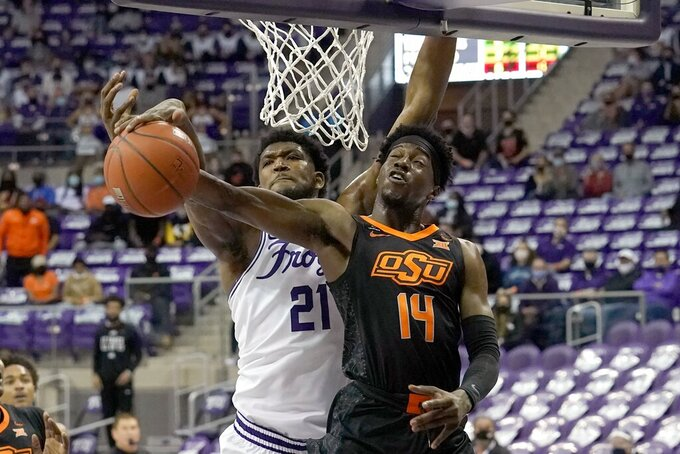 TCU center Kevin Samuel (21) blocks a shot by Oklahoma State guard Bryce Williams (14) during the first half of an NCAA college basketball game in Fort Worth, Texas, Wednesday, Feb. 3, 2021. (AP Photo/Tony Gutierrez)