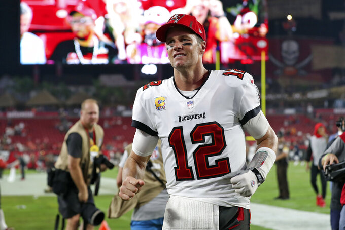 Tampa Bay Buccaneers quarterback Tom Brady (12) smiles as he runs off the field after an NFL football game against the Chicago Bears Sunday, Oct. 24, 2021, in Tampa, Fla. (AP Photo/Mark LoMoglio)