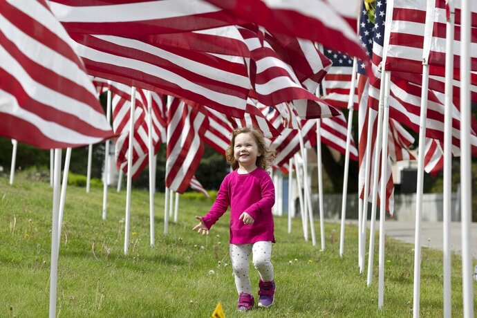 Hazel Roberts walks in a field of flags ahead of Memorial Day, Saturday, May 23, 2020, in Cohasset, Mass. (AP Photo/Michael Dwyer)