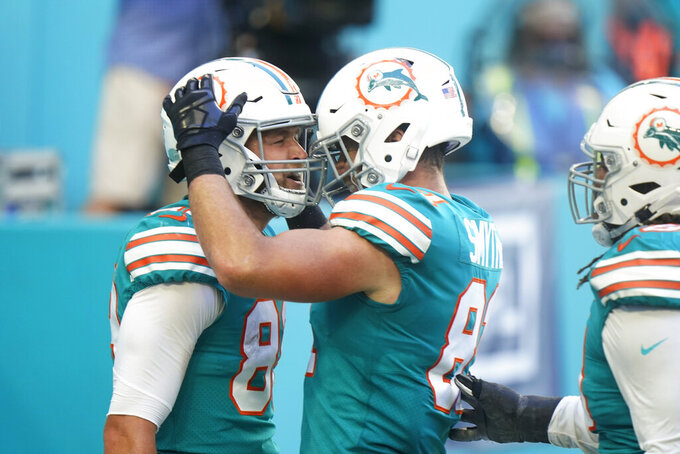 Miami Dolphins tight end Durham Smythe (81), right, congratulates tight end Mike Gesicki (88) after Gesicki scored a touchdown, during the first half of an NFL football game against the Kansas City Chiefs, Sunday, Dec. 13, 2020, in Miami Gardens, Fla. (AP Photo/Wilfredo Lee)