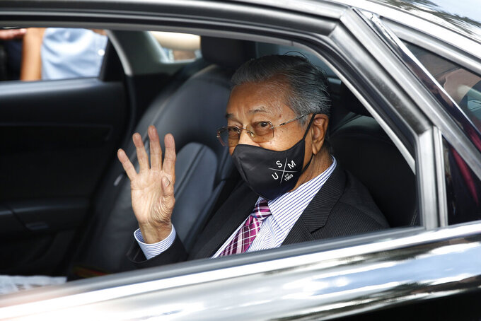 Malaysia's former Prime Minister Mahathir Mohamad waves as he leaves national palace in Kuala Lumpur, Malaysia, Tuesday, April 20, 2021. Malaysian opposition lawmakers, led by Mahathir, submitted a petition to the country's king on Tuesday seeking an end to a coronavirus emergency so Parliament can resume. (AP Photo/FL Wong)