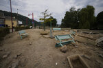 Chairs are upended and debris is scattered in a square after flooding in Vaux-sous-Chevremont, Belgium, Saturday, July 24, 2021. Residents were still cleaning up after heavy rainfall hit the country causing flooding in several regions. (AP Photo/Virginia Mayo)