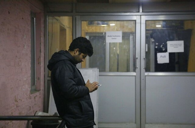 A man checks his cellphone outside a media facilitation centre in Srinagar, Indian controlled Kashmir, Tuesday, Dec. 31, 2019. Authorities in Indian-controlled Kashmir will restore text messaging services in the disputed region on Wednesday, almost five months after India's government downgraded its semi-autonomy and imposed a strict security and communications lockdown, an official said Tuesday. (AP Photo/Mukhtar Khan)