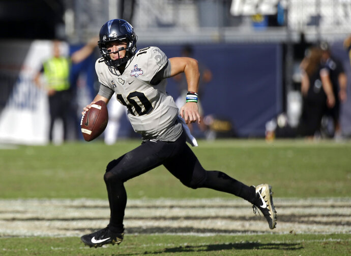 FILE - In this Dec. 2, 2017, file photo, Central Florida quarterback McKenzie Milton scrambles during the second half of the American Athletic Conference championship NCAA college football game against Memphis, in Orlando, Fla. Most of the playmakers return from one of the best offenses in the country, including gifted quarterback McKenzie Milton. (AP Photo/John Raoux, File)