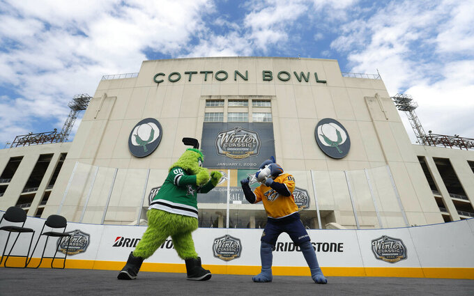 Mascots for the Nashville Predators, right, and the Dallas Stars pose for a photo in front of the Cotton Bowl in Dallas, Wednesday, March 20, 2019. The NHL Winter Classic hockey game between the Nashville Predators and the Dallas Stars will be played Jan. 1, 2020, at the Cotton Bowl at Fair Park in Dallas. (AP Photo/LM Otero)