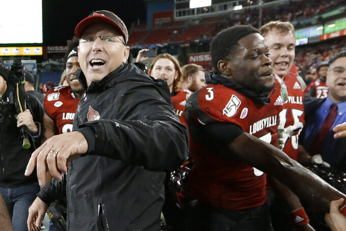 Louisville head coach Scott Satterfield, left, and quarterback Micale Cunningham (3) celebrate in the final moments of the fourth quarter of Louisville's win over Mississippi State in the Music City Bowl NCAA college football game Monday, Dec. 30, 2019, in Nashville, Tenn. Louisville won 38-28. (AP Photo/Mark Humphrey)