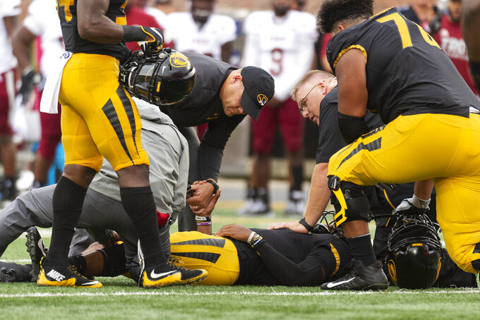 Missouri head coach Barry Odom, top, holds the hand of his quarterback Kelly Bryant as he lays on the field after he was injured during the second quarter of an NCAA college football game against Troy Saturday, Oct. 5, 2019, in Columbia, Mo. (AP Photo/L.G. Patterson)