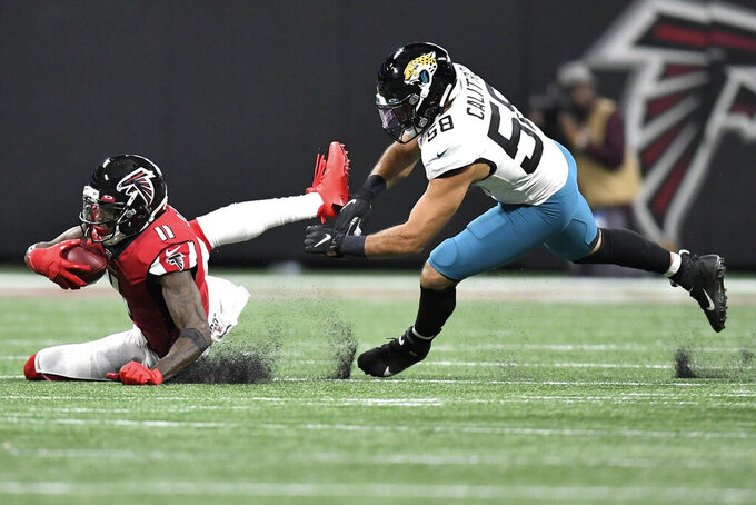 Atlanta Falcons wide receiver Julio Jones (11) makes the catch agaijst Jacksonville Jaguars linebacker Austin Calitro (58) during the first half of an NFL football game, Sunday, Dec. 22, 2019, in Atlanta (AP Photo/Danny Karnik)