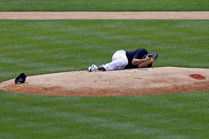 New York Yankees pitcher Masahiro Tanaka lies on the field after being hit by a ball off the bat of Yankees Giancarlo Stanton during a baseball a workout at Yankee Stadium in New York, Saturday, July 4, 2020. (AP Photo/Adam Hunger)