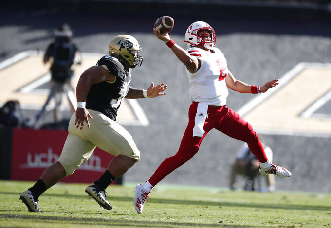 Nebraska quarterback Adrian Martinez, right, launches a pass with Colorado defensive end Mustafa Johnson in pursuit in the second half of an NCAA college football game Saturday, Sept. 7, 2019, in Boulder, Colo. Colorado won 34-31 in overtime. (AP Photo/David Zalubowski)