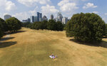 A man sunbathes amidst patches of dried out lawn from a lack of rain in Atlanta, Thursday, Oct. 3, 2019. Scientists say more than 45 million people across 14 Southern states are now in the midst of a drought that's cracking farm soil, drying up ponds and raising the risk of wildfires. (AP Photo/David Goldman)