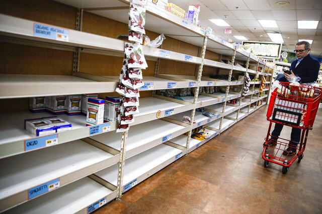 Shoppers browse barren shelves at a supermarket, Friday, March 13, 2020, in Larchmont, N.Y. State officials have set up a