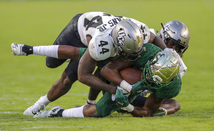 Central Florida's Nate Evans (44) tackles South Florida's Stanley Clerveaux during the second half of an NCAA college football game Friday, Nov. 23, 2018, in Tampa, Fla. (AP Photo/Mike Carlson)