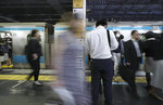 Commuters get on and off a train at a station Wednesday, May 22, 2019, in Tokyo. A police-developed smartphone app with anti-sex crime alarms has won massive subscriptions as Japanese women try to arm themselves against gropers on packed rush-hour trains. (AP Photo/Eugene Hoshiko)
